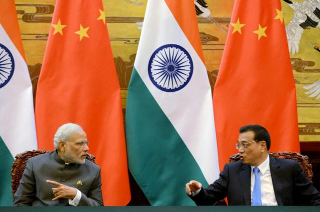 Indian Prime Minister Narendra Modi (L) talks with Chinese Premier Li Keqiang during a signing ceremony at the Great Hall of the People in Beijing, China, May 15, 2015. REUTERS/Kenzaburo Fukuhara/Pool