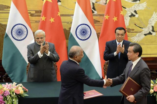 Indian Prime Minister Narendra Modi, rear left, and Chinese Premier Li Keqiang, rear right, applaud during a signing ceremony at the Great Hall of the People in Beijing, China on May 15, 2015. Friday, May 15, 2015. (Kenzaburo Fukuhara/Pool Photo via AP)
