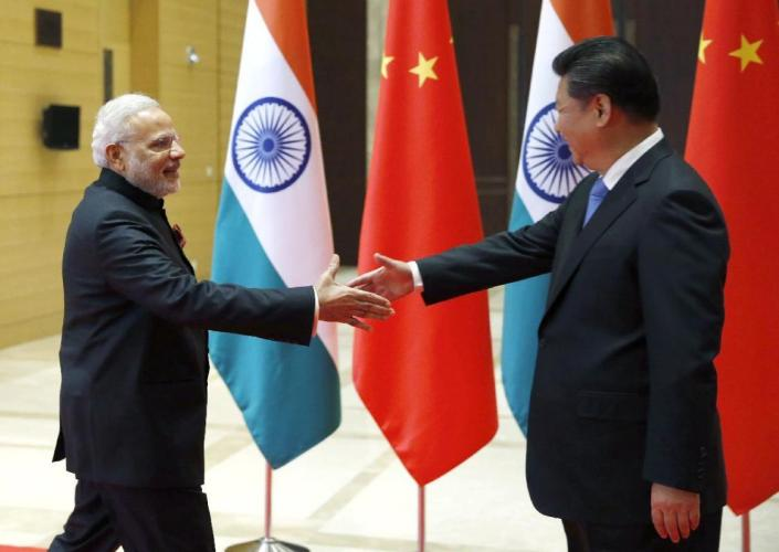 Indian Prime Minister Narendra Modi, left, is welcomed by Chinese President Xi Jinping prior to their meeting in Xian, Shaanxi province, China, Thursday, May 14, 2015. Modi is visiting China this week to build friendship between the two Asian giants despite a long history of disputes and rivalries, along with some areas of cooperation, especially in the economic sphere. (Kim Kyung-Hoon/Pool Photo via AP)