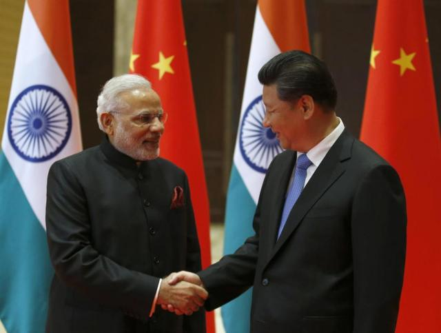 Indian Prime Minister Narendra Modi, left, and Chinese President Xi Jinping shake hands prior to their meeting in Xian, Shaanxi province, China, Thursday, May 14, 2015. Modi is visiting China this week to build friendship between the two Asian giants despite a long history of disputes and rivalries, along with some areas of cooperation, especially in the economic sphere. (Kim Kyung-Hoon/Pool Photo via AP)