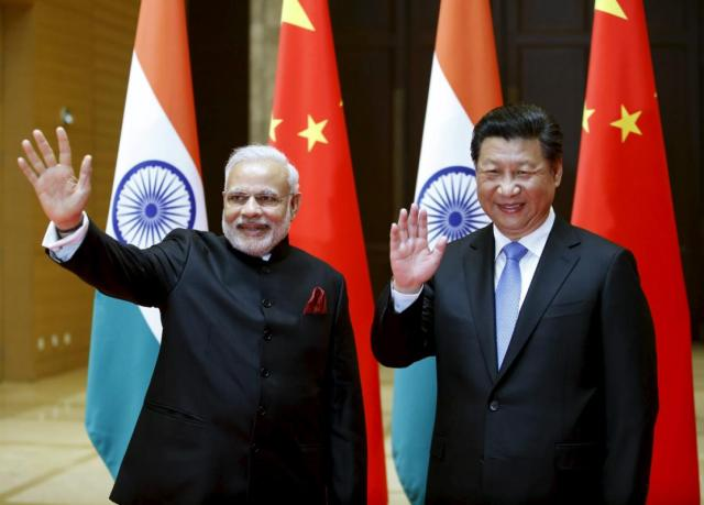 Indian Prime Minister Narendra Modi (L) and Chinese President Xi Jinping wave to journalists before they hold a meeting in Xian, Shaanxi province, China, May 14, 2015.  REUTERS/Kim Kyung-Hoon        TPX IMAGES OF THE DAY