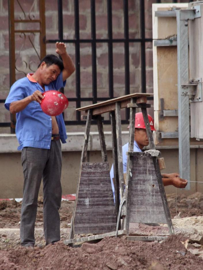 In this photo taken on May 20, 2015, Chinese workers at the building site of a new hotel to be used by Congo government officials when completed in Kinshasa, Democratic Republic of Congo. Congo's government is bringing in outside experts including officials from the World Bank and the United Nations, to investigate the long-term impact of some $6.7 billion in contracts with Chinese companies that critics have said could exploit the central African nation's mineral riches. (AP Photo/John Bompengo)