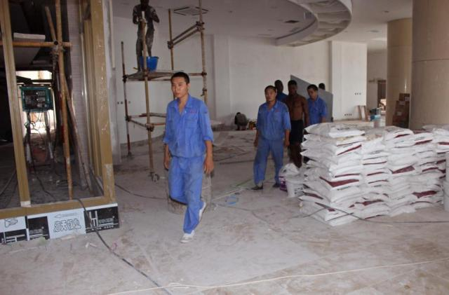 In this photo taken on May 20, 2015, Chinese workers inside a new hotel being built for the use by  Congo government officials when completed in Kinshasa, Democratic Republic of Congo.  Congo's government is bringing in outside experts including officials from the World Bank and the United Nations, to investigate the long-term impact of some $6.7 billion in contracts with Chinese companies that critics have said could exploit the central African nation's mineral riches.(AP Photo/John Bompengo)