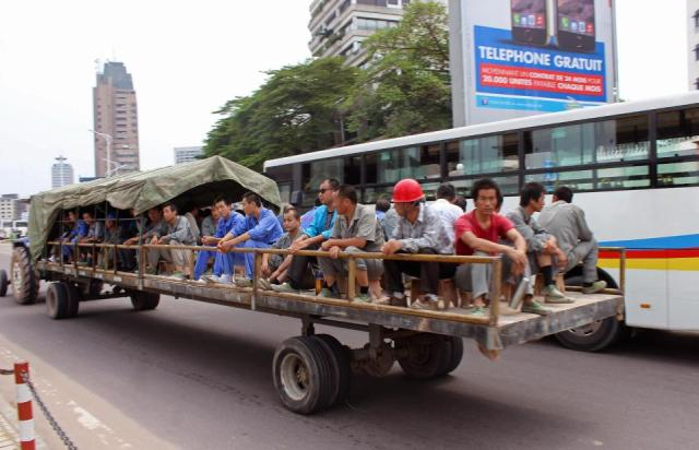 In this photo taken on May 20, 2015, Chinese workers travel on the back of a trailer pulled by a tractor  on their way to work in Kinshasa, Democratic Republic of Congo.  Congo's government is bringing in outside experts including officials from the World Bank and the United Nations, to investigate the long-term impact of some $6.7 billion in contracts with Chinese companies that critics have said could exploit the central African nation's mineral riches.(AP Photo/John Bompengo)