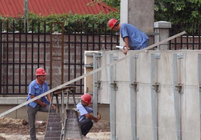 In this photo taken on May 20, 2015, Chinese workers at the building site of a new hotel to be used by Congo government officials when completed in Kinshasa, Democratic Republic of Congo. Congo's government is bringing in outside experts including officials from the World Bank and the United Nations, to investigate the long-term impact of some $6.7 billion in contracts with Chinese companies that critics have said could exploit the central African nation's mineral riches.(AP Photo/John Bompengo)
