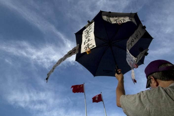 A pro-democracy protester holds an umbrella, symbol of the Occupy Central movement, during a march to demand lawmakers reject a Beijing-vetted electoral reform package for the city's first direct chief executive election, under Chinese (L) and Hong Kong's flags outside Legislative Council in Hong Kong, China June 14, 2015. Talks between Chinese officials and Hong Kong democrats ended in stalemate on May 31, with democrats sticking by plans to veto a Beijing-proposed election blueprint in a mid-June vote that could become a flashpoint for pro-democracy protests. REUTERS/Tyrone Siu