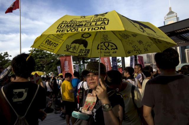 A pro-democracy protester holds a umbrella, the symbol of the Occupy Central movement, during a march to demand lawmakers reject a Beijing-vetted electoral reform package for the city's first direct chief executive election, near a Hong Kong flag (top L) outside the Legislative Council building in Hong Kong, China June 14, 2015. Thousands of people took to the streets of Hong Kong on Sunday to protest against electoral reforms approved by Beijing to choose the city's next leader, the beginning of several days of demonstrations before the reforms go to a vote. REUTERS/Tyrone Siu