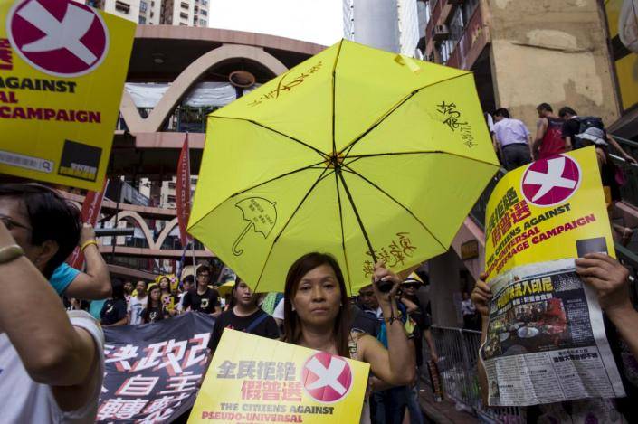 A pro-democracy protester holds a yellow umbrella, the symbol of the Occupy Central movement, during a march to demand lawmakers reject a Beijing-vetted electoral reform package for the city's first direct chief executive election in Hong Kong, China June 14, 2015. Thousands of people took to the streets of Hong Kong on Sunday to protest against electoral reforms approved by Beijing to choose the city's next leader, the beginning of several days of demonstrations before the reforms go to a vote. REUTERS/Tyrone Siu