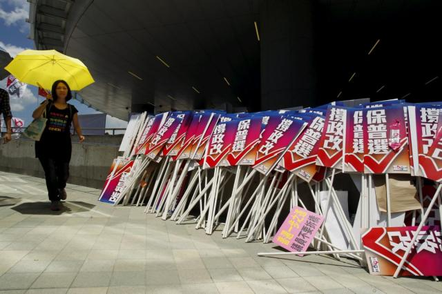 "A pro-democracy protester carrying a yellow umbrella, symbol of the Occupy Central movement, walks past placards which read ""support electoral reform"", belonging to pro-China supporters, outside Legislative Council in Hong Kong, China June 17, 2015. Hong Kong lawmakers began a debate on Wednesday on a Beijing-backed electoral reform proposal that will define the city's democratic future and could trigger fresh protests in the Chinese-controlled city.   REUTERS/Liau Chung-ren"