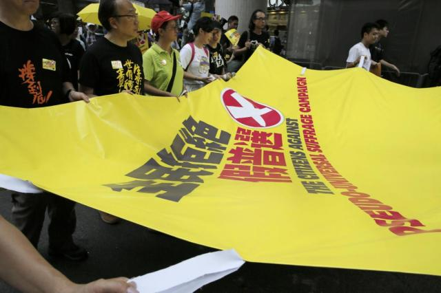 "Protesters carry a huge yellow banner reads "" The citizens against pseudo-universal suffrage campaign "" during a rally as people march in a downtown street to support for a veto of the government's electoral reform package in Hong Kong, Sunday, June 14, 2015. The rally was held ahead of a crucial vote by lawmakers on Beijing-backed election reforms that sparked huge street protests last year.  (AP Photo/Vincent Yu)"