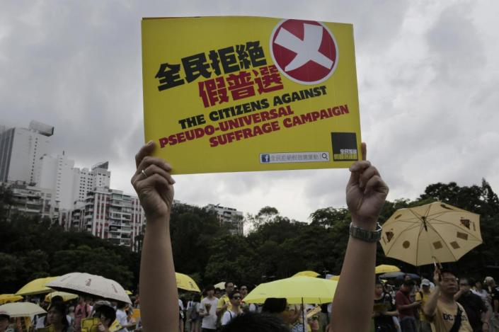 A protester raises a placard as people march in a downtown street to support for a veto of the government's electoral reform package in Hong Kong, Sunday, June 14, 2015. The rally was held ahead of a crucial vote by lawmakers on Beijing-backed election reforms that sparked huge street protests last year. (AP Photo/Vincent Yu)