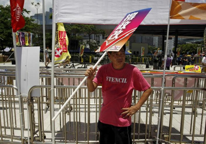"A pro-China supporter uses a placard which reads ""support electoral reform"" to cover himself from the sun during a demonstration outside Legislative Council in Hong Kong, China June 17, 2015. Hong Kong lawmakers began a debate on Wednesday on a Beijing-backed electoral reform proposal that will define the city's democratic future and could trigger fresh protests in the Chinese-controlled city.   REUTERS/Liau Chung-ren"