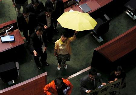 Pro-democracy lawmaker Claudia Mo carrying a yellow umbrella, a symbol of the Occupy Central movement, leaves after voting at the Legislative Council in Hong Kong, China June 18, 2015. REUTERS/Bobby Yip