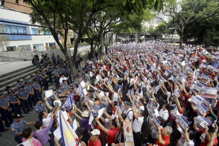 Protesters face the Chinese Consulate to display their anti Chinese message during a Philippines Independence Day rally in the financial district of Makati city east of Manila, Philippines, Friday, June 12, 2015. The protesters condemned the recent reclamation of land by China in the disputed Spratlys group of islands on the South China Sea. (AP Photo/Bullit Marquez)