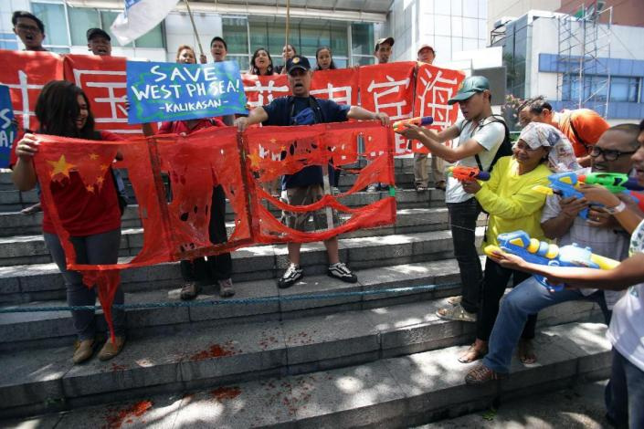 Filipino environmental activists aim water guns at mock Chinese flags as they stage a rally outside the Chinese Consulate in suburban Makati, south of Manila, Philippines on Monday, May 11, 2015 to protest against the continued building of infrastructures along a disputed group of islands known as the Spratlys in the South China Sea. The group is accusing the Chinese military of destroying the fragile ecosystem and livelihood of fishermen during their reclamation projects in the area which both countries have claimed ownership. (AP Photo/Aaron Favila)