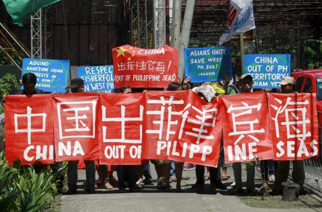 Environmental activists display placards as they march towards the Chinese Embassy in Makati City, Metro Manila May 11, 2015. The activists demanded that Chinese authorities immediately put a stop to the ecological destruction caused by the reclamation activities of China in the South China Sea, which the Philippines calls West Philippine Sea. They also condemned what they say is the bullying by Chinese naval and coast guard forces of Filipino fishermen in the disputed seas, a environmental activist said. REUTERS/Romeo Ranoco