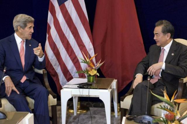 US Secretary of State John Kerry (L) and China's Foreign Minister Wang Yi talk before a bilateral meeting at the Putra World Trade Center August 5, 2015 in Kuala Lumpur, Malaysia.  REUTERS/Brendan Smialowski/Pool
