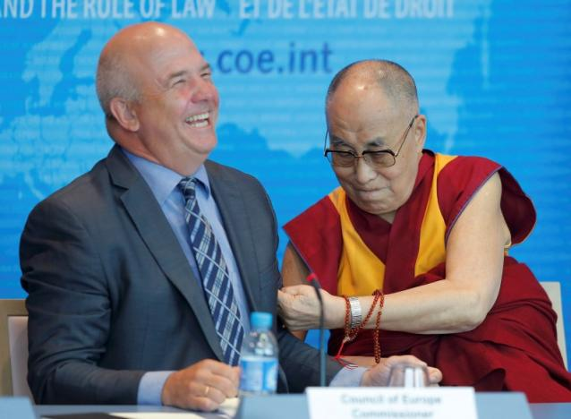 Tibet's exiled spiritual leader the Dalai Lama (R) jokes with Nils Muiznieks, Commissioner for Human Rights of the Council of Europe, during his visit at the Council of Europe in Strasbourg, France, September 15, 2016.  REUTERS/Vincent Kessler