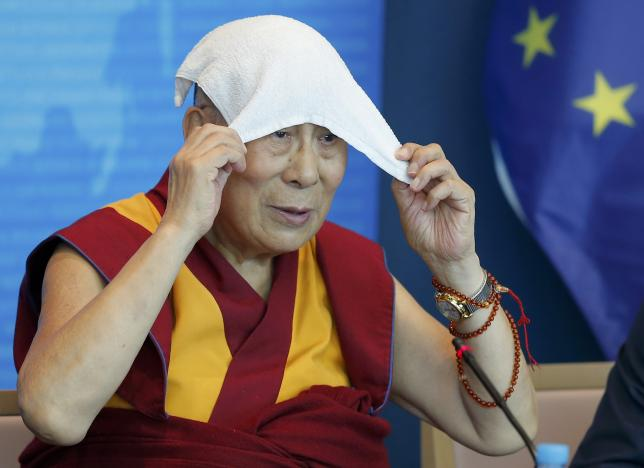 Tibet's exiled spiritual leader the Dalai Lama puts a towel on his head during a visit at the Council of Europe in Strasbourg, France, September 15, 2016. REUTERS/Vincent Kessler